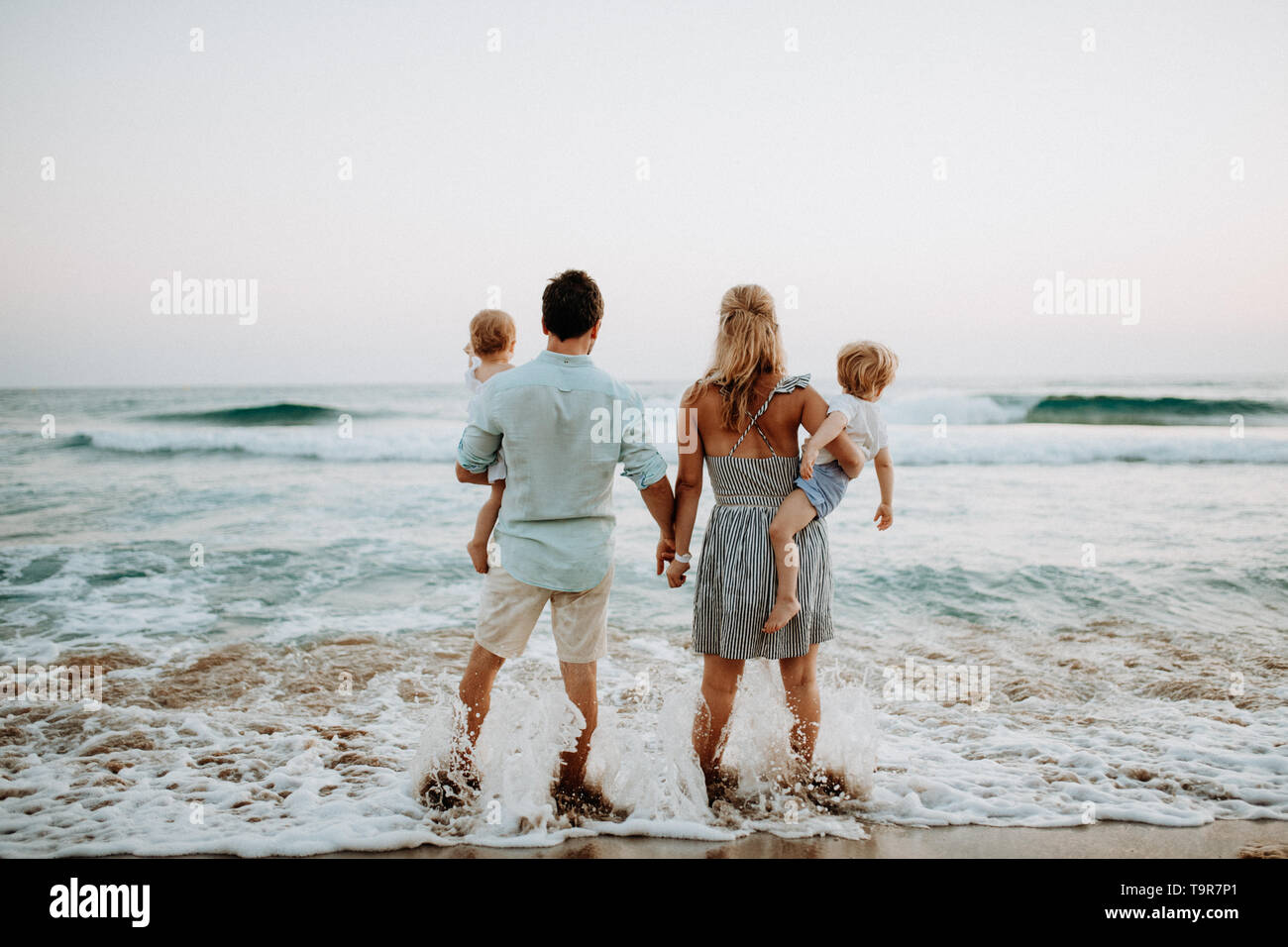A rear view of family with two toddler children standing on beach on summer holiday. - Stock Image