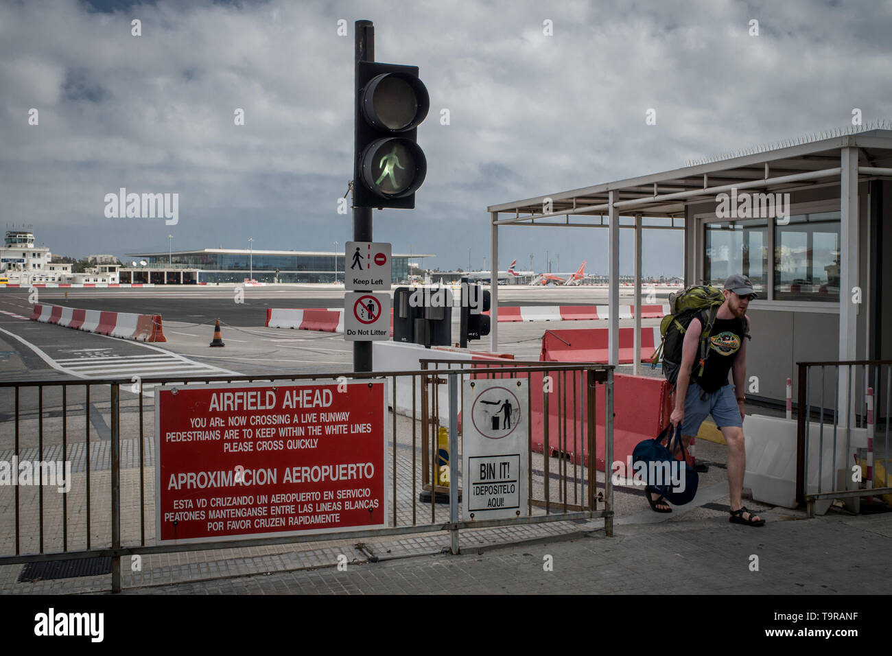 A man crossing at Gibraltar international airport  (British overseas territory) near the border with Spain. - Stock Image