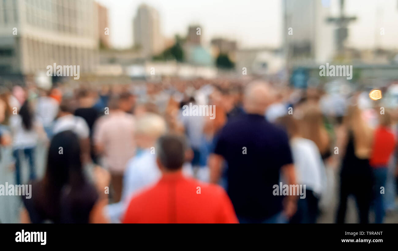 Out of focus image of big crowd of people walking on the city street - Stock Image