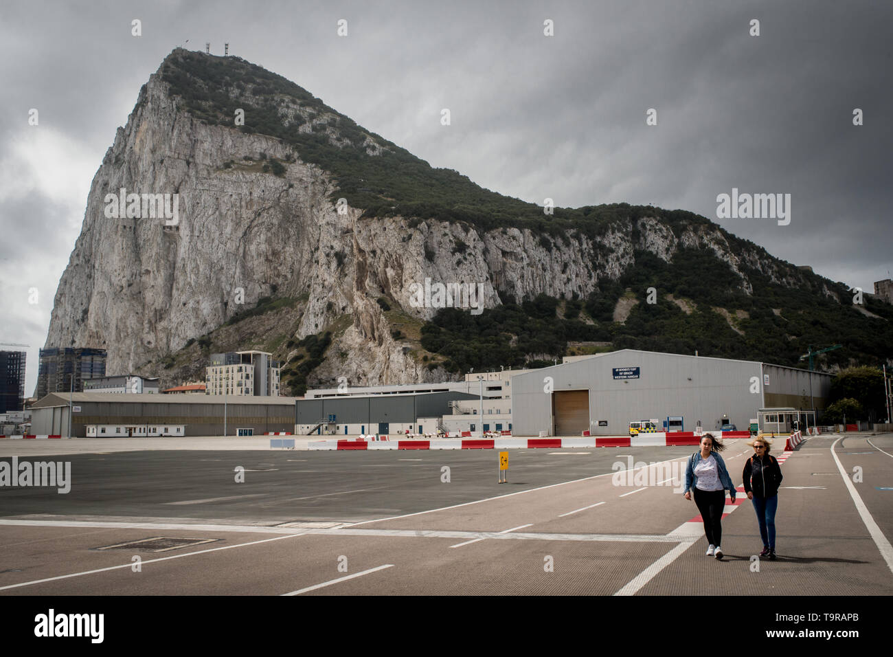 Pedestrians crossing  the asphalt at Gibraltar international airport  (British overseas territory)  near the border with Spain. - Stock Image