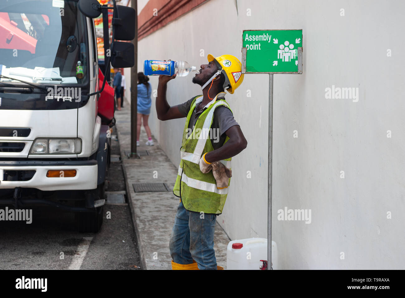 04.04.2018, Singapore, Republic of Singapore, Asia - A labourer is standing on the roadside in Chinatown drinking water from a bottle. - Stock Image