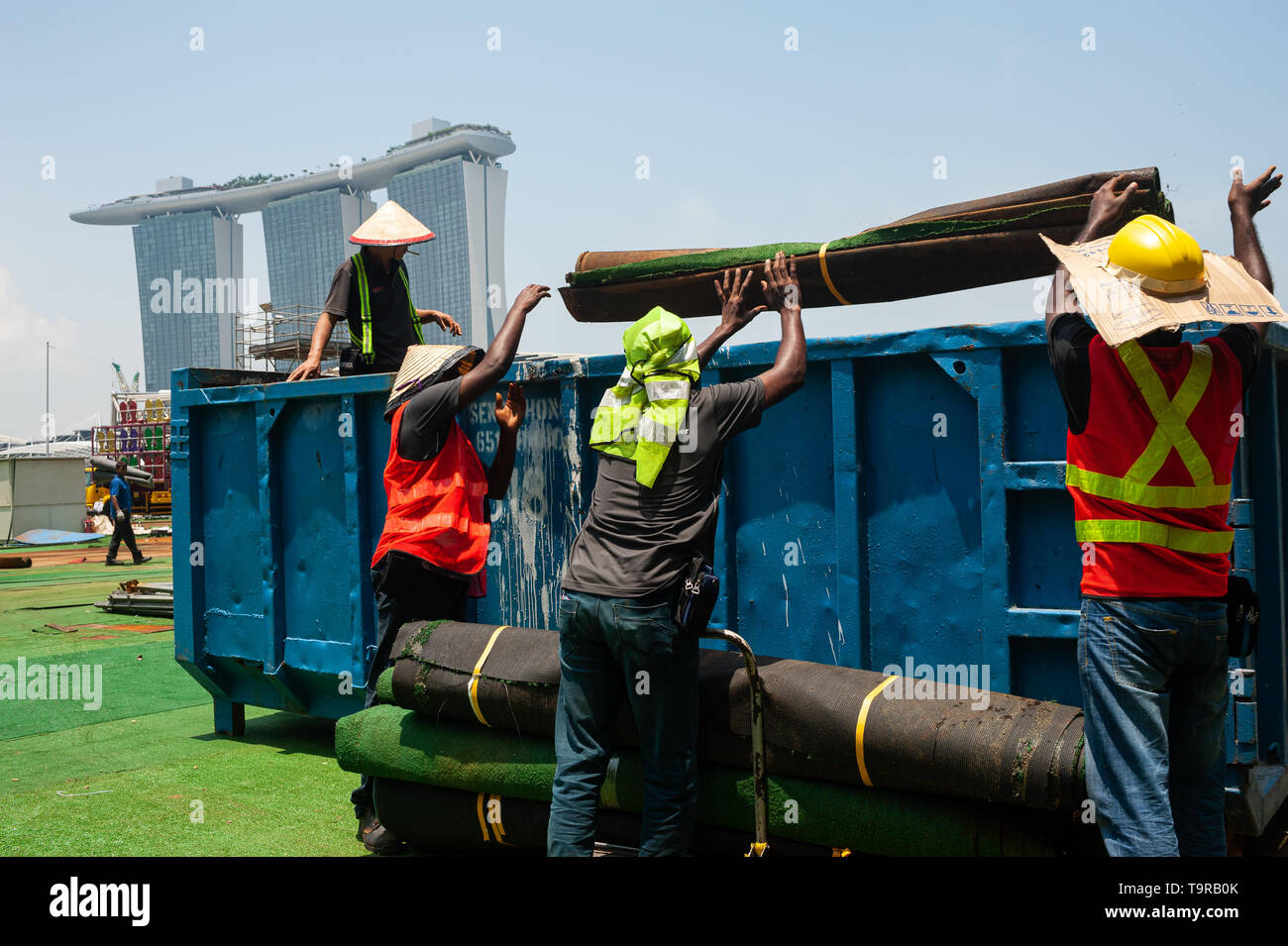 04.04.2018, Singapore, Republic of Singapore, Asia - Workers are seen disposing of artificial turf in Marina Bay with the Marina Bay Sands Hotel in th - Stock Image