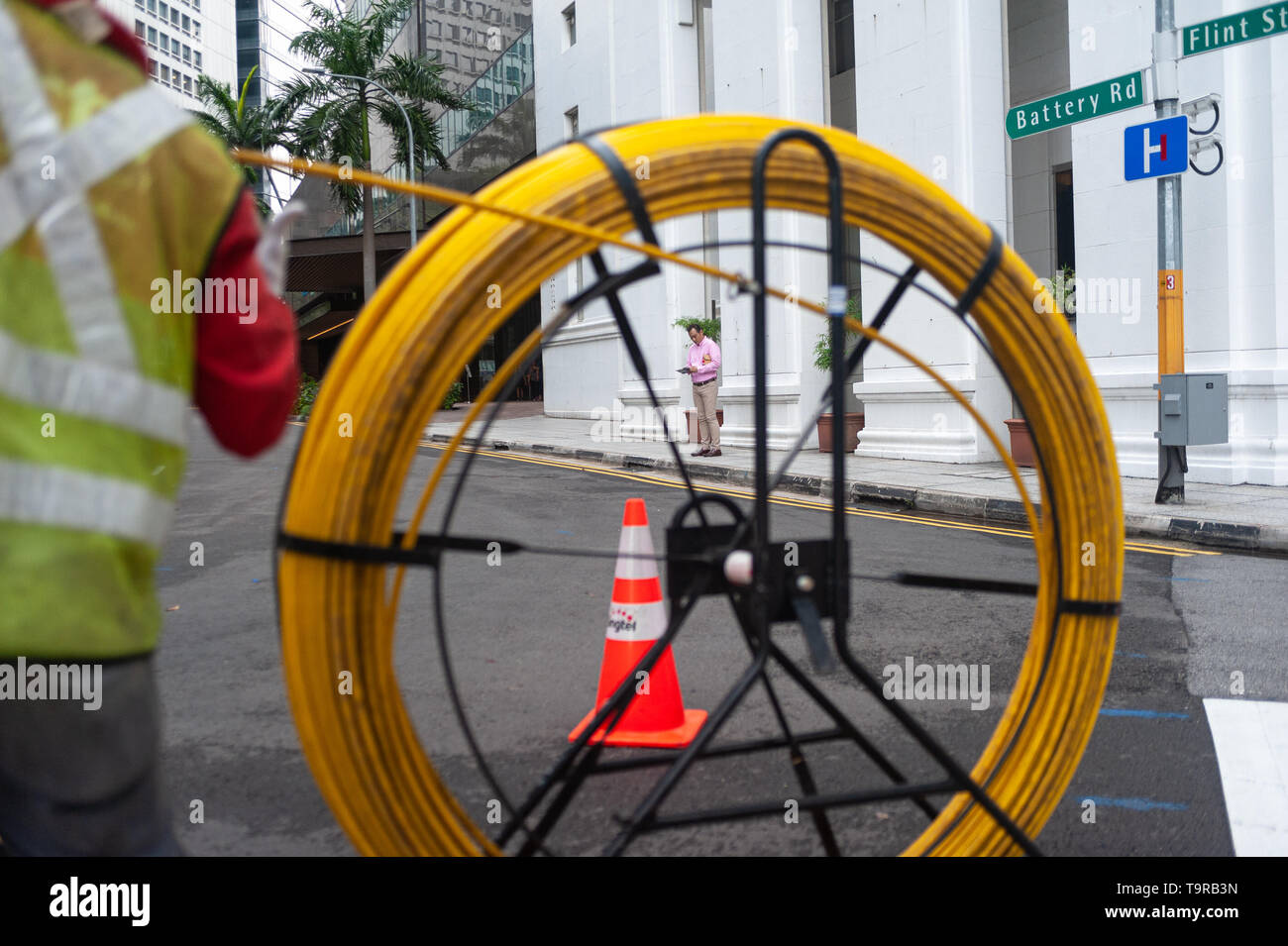 15.04.2018, Singapore, Republic of Singapore, Asia - A worker is laying cables on a road in the central business district. - Stock Image