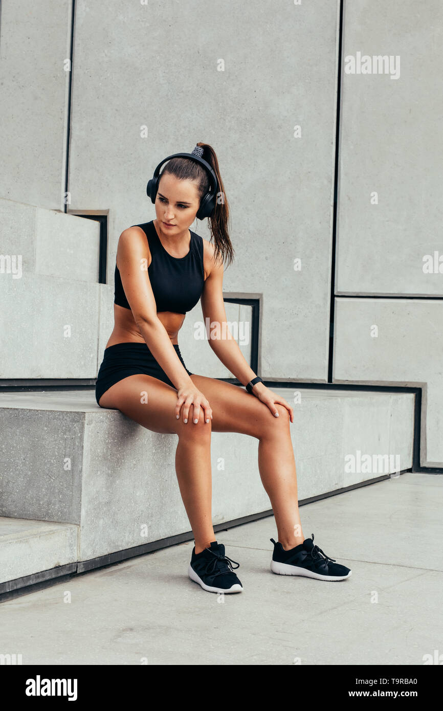 Fit young woman with headphones sitting on steps after physical training. Woman taking break after exercising session outdoors. - Stock Image