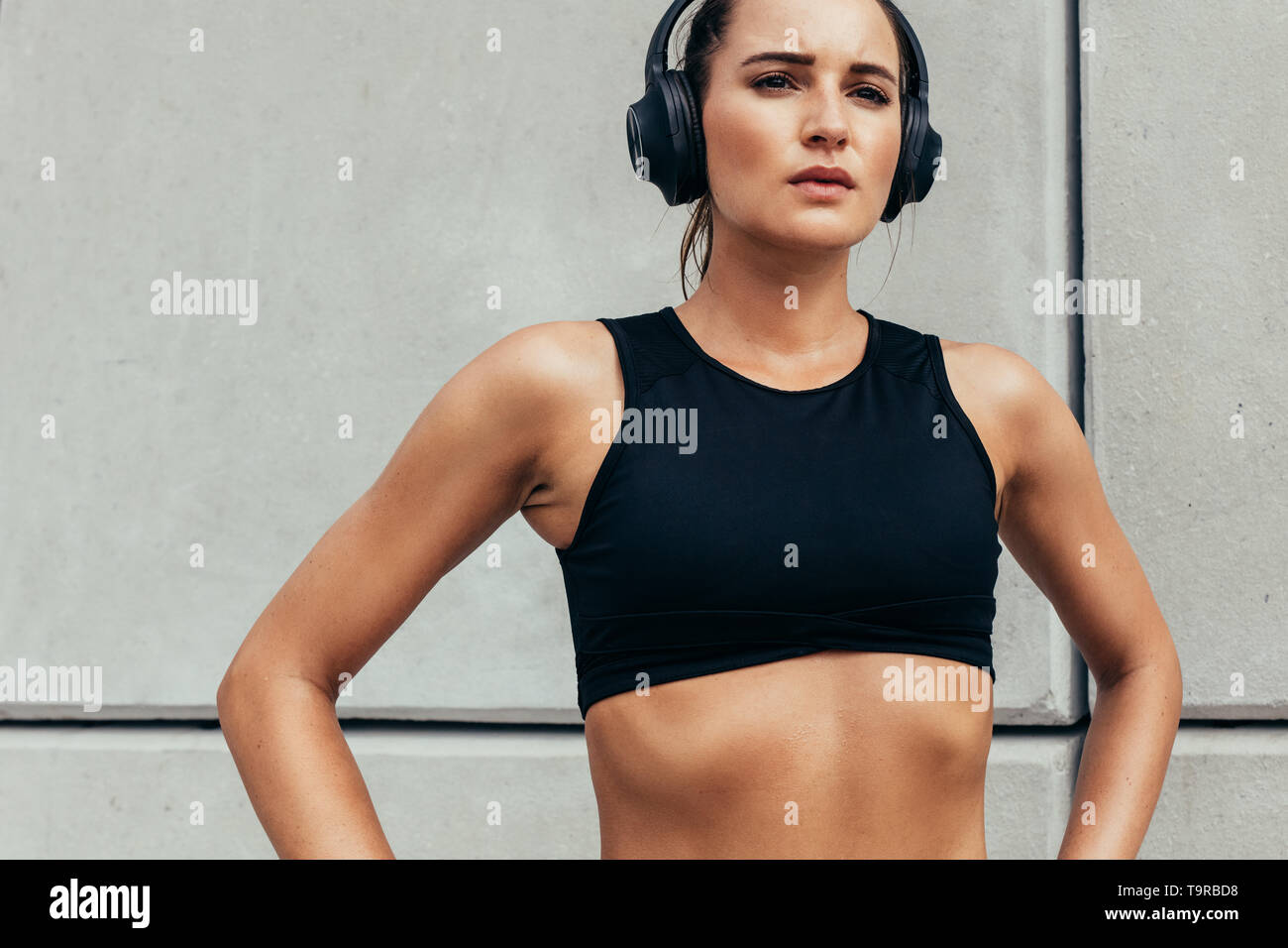 Confident sportswoman standing with her hands on hips and looking away. Fitness girl with headphones on taking break after workout. - Stock Image