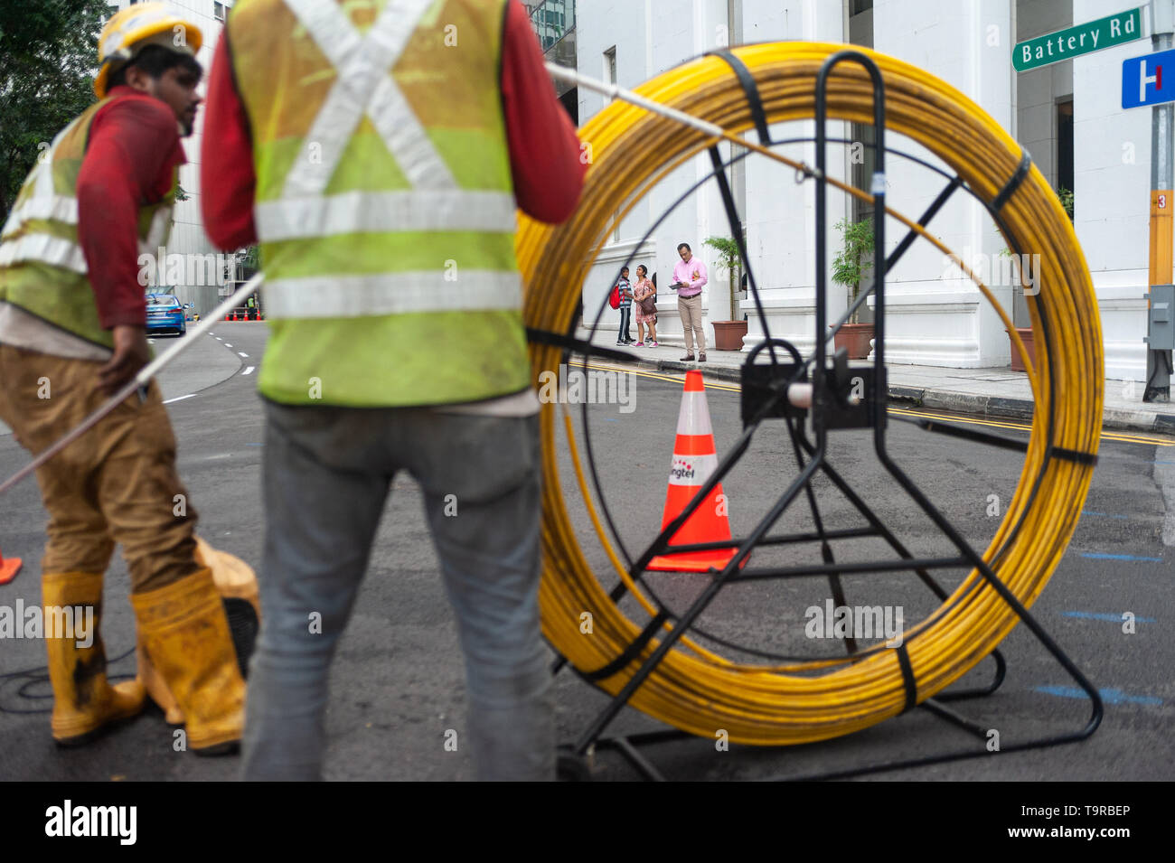 15.04.2018, Singapore, Republic of Singapore, Asia - Two workers are laying cables on a road in the central business district. - Stock Image