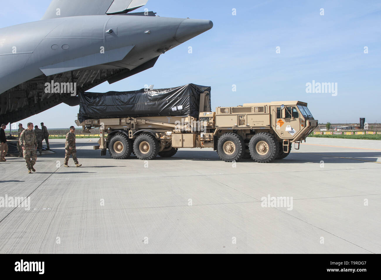 MIHAIL KOGALNICEANU (MK) AIR BASE, ROMANIA - American troops offload a Terminal High Altitude Area Defense (THAAD) launcher from a C-17 Globemaster III at Mihail Kogalniceanu (MK) Air Base, Romania, May 3, 2019. The THAAD deployed to Romania from 69th Air Defense Artillery Brigade, 32nd Army Air and Missile Defense Command out of Fort Hood, Texas. The deployment of the THAAD is in support of the NATO Ballistic Missile Defense mission and reinforces the strong and unremitting U.S. commitment to the defense of our NATO allies. - Stock Image
