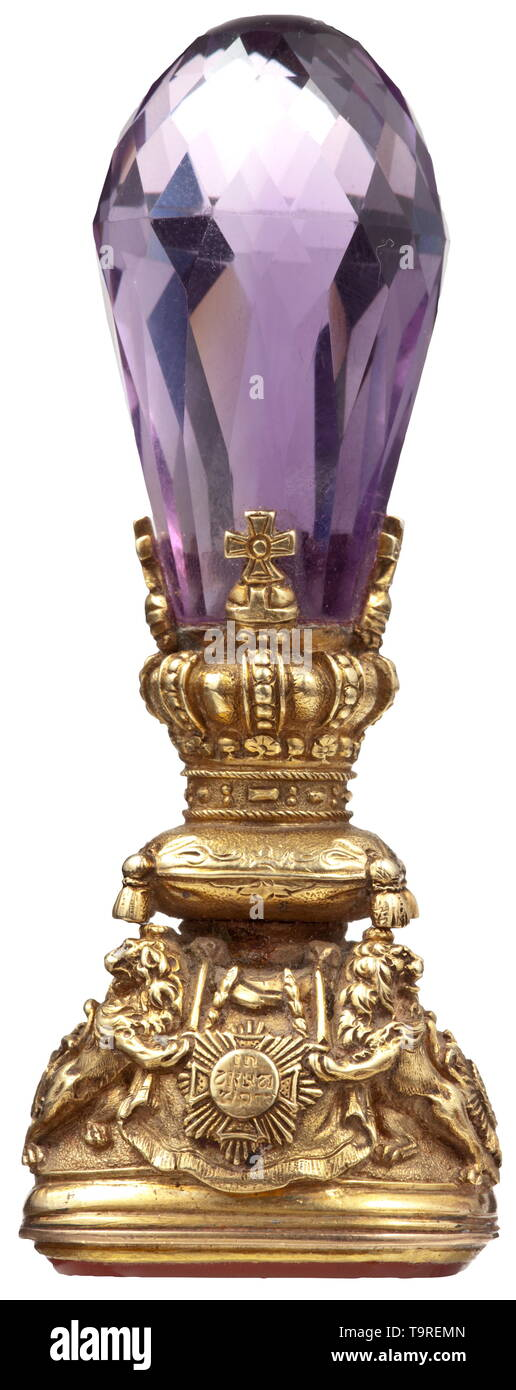 King Ludwig II of Bavaria (1845 - 1886) - a royal sea l Golden mounting decorated in relief, the handle formed of a large cut amethyst, the seal surface made from a rectangular carnelian with the deeply chiselled, large Bavarian state coat of arms above the collars of the order, surmounted by the ermine coat and crown. The golden mounting consists of the Bavarian royal crown on the coronation cushion, carried by the Bavarian lions armed with swords, with the House Knight's Order of St. Hubert, the Military House Knight's Order of St. George, the , Additional-Rights-Clearance-Info-Not-Available - Stock Image