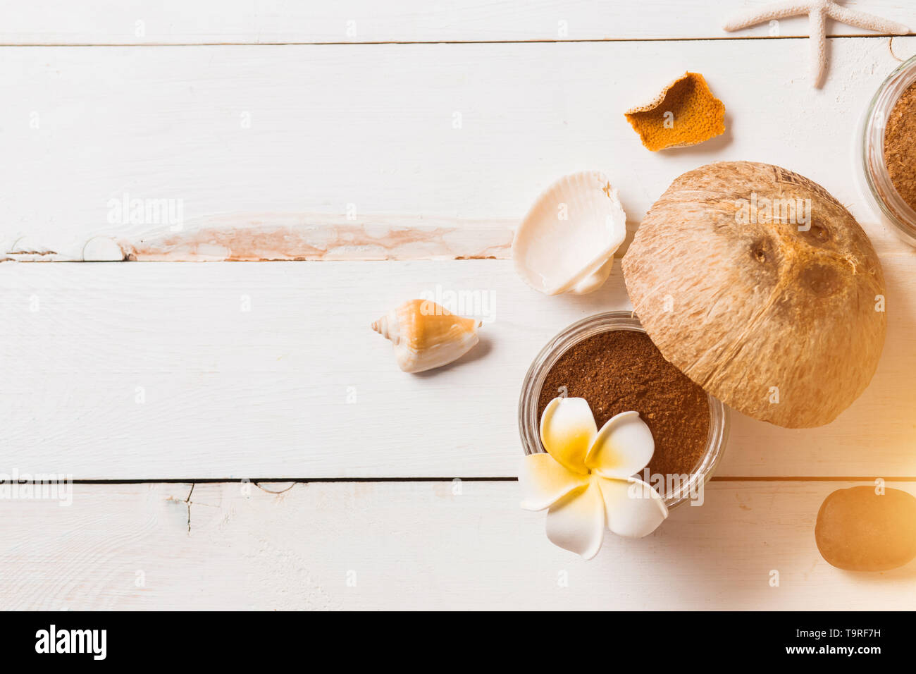 Spa decoration, natural organic body care products. Beautiful composition with coconut, coffee scrub, flower, sea shell, white towel on vintage wooden Stock Photo
