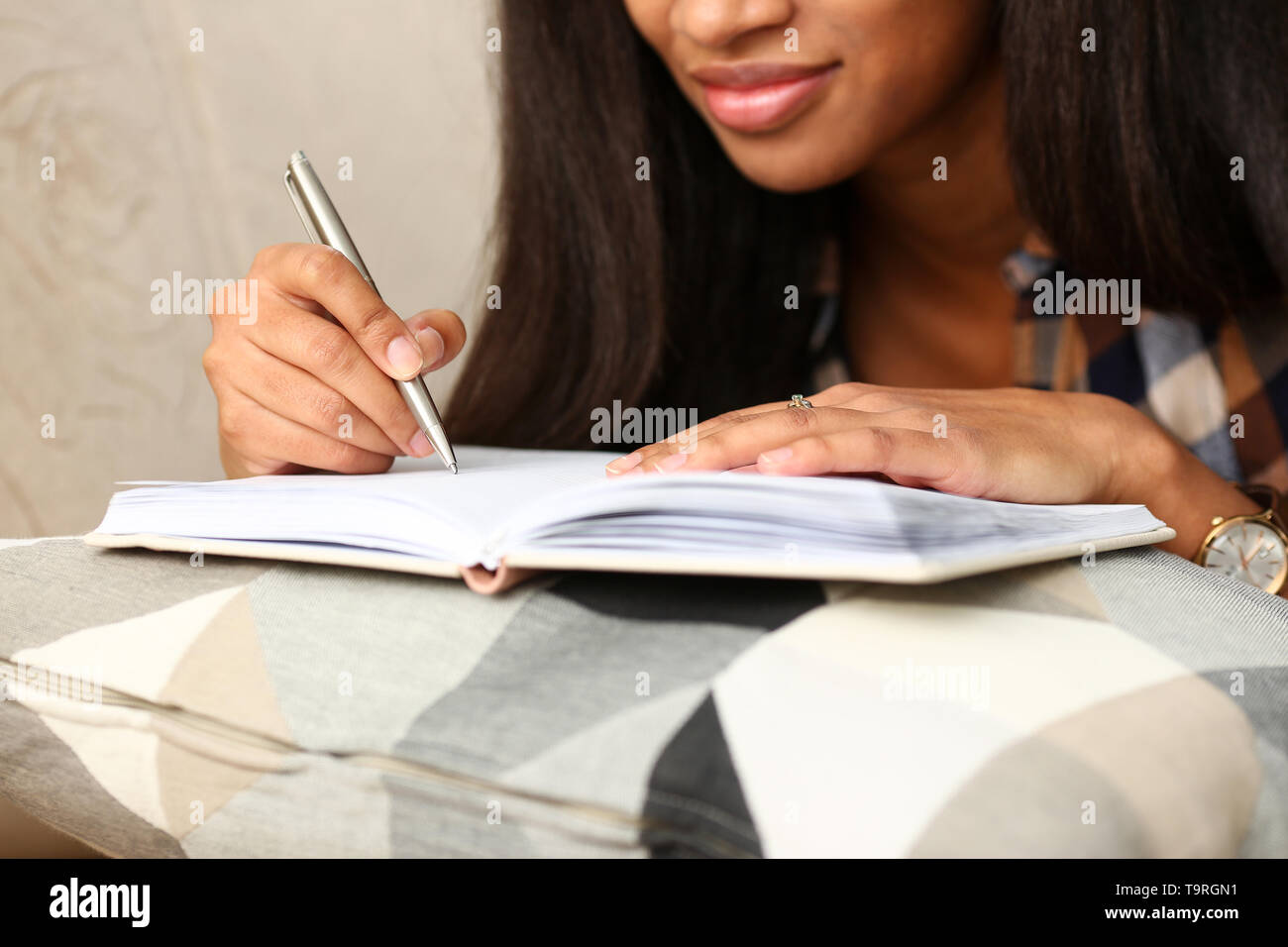 Arm of black woman write story in notebook - Stock Image
