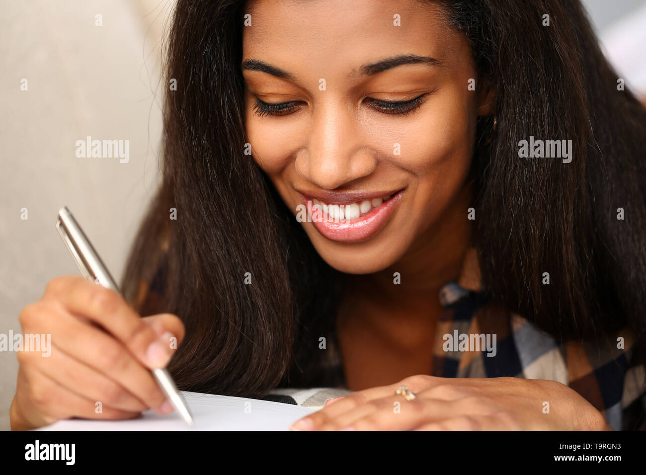 Smiling black woman write story in notebook - Stock Image
