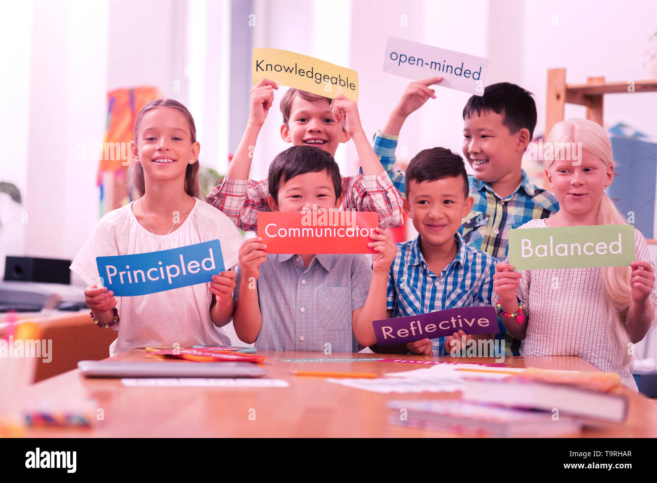 Children of different races holding colorful adjectives. - Stock Image