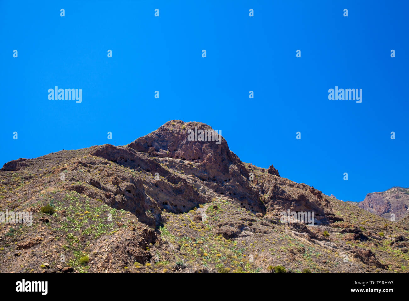 Gran Canaria, the largest aboriginal cave villages on Canary Islands Montana de los Huesos, Bones Mountain, mutliple caves visible in the soft layer o - Stock Image