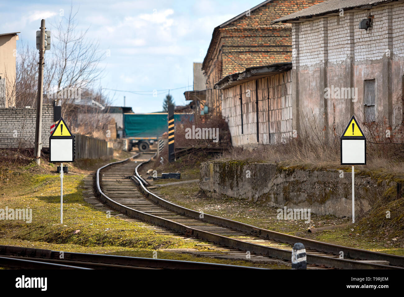 Triangular road sign mockup at railway line warning about damaged rail section and oversized narrow passage for trains. - Stock Image