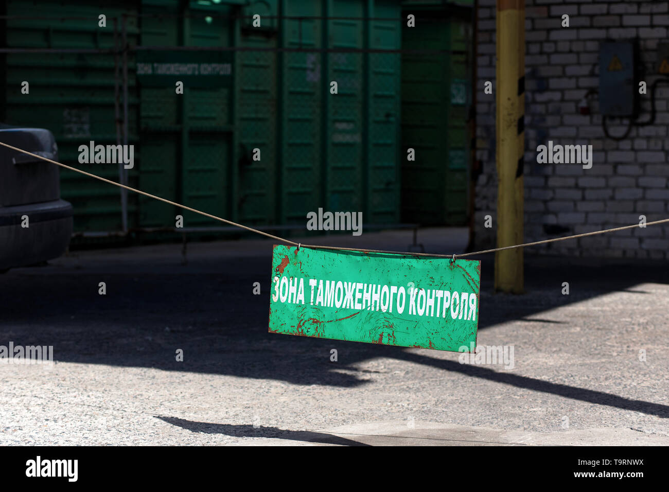 Green old rusty customs area sign at entrance to customs clearance with the inscription in Russian with freight railcar at background. Russian transla - Stock Image