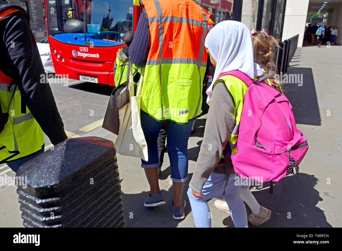 London, England, UK. Schoolchildren waiting to get on a bus - young girl wearing a headscarf - Stock Image