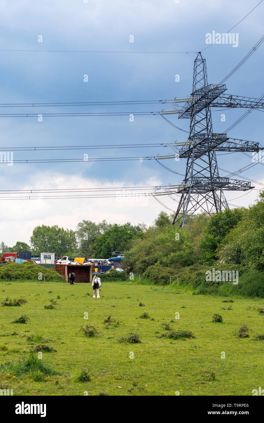 View across a field of a large electricity pylon, power lines and car scrapyard in Nursling, Test Valley, Southampton, Hampshire, southern England, UK Stock Photo