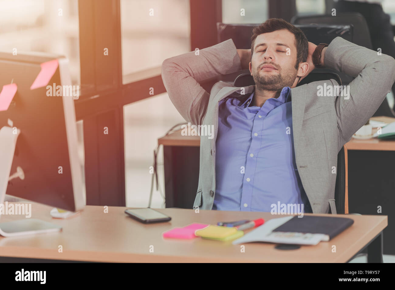 businessman relaxing rest nap after hard work day in the office - Stock Image