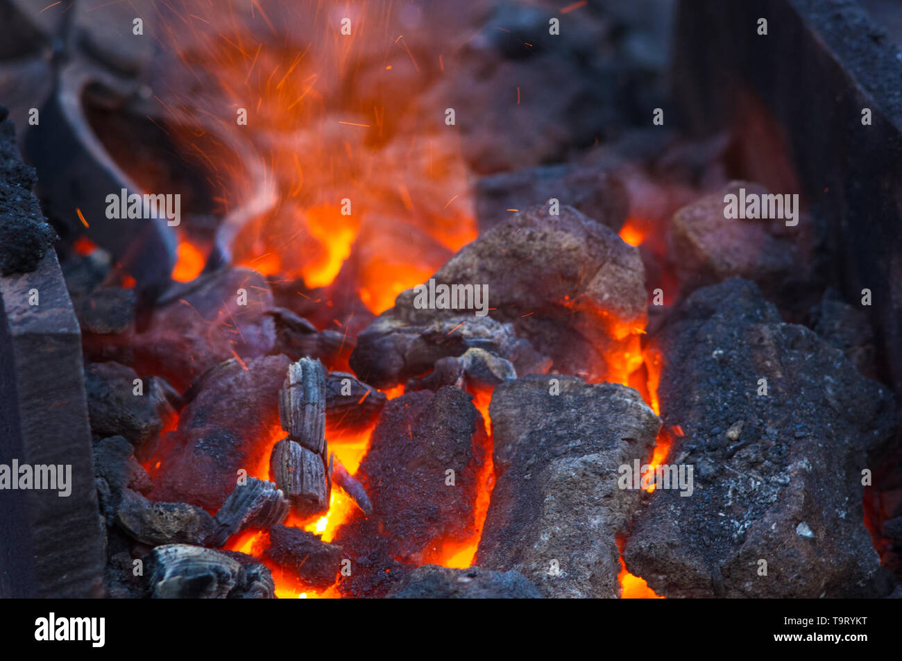 blacksmith furnace with burning coals, tools, and glowing hot metal workpieces, close-up - Stock Image