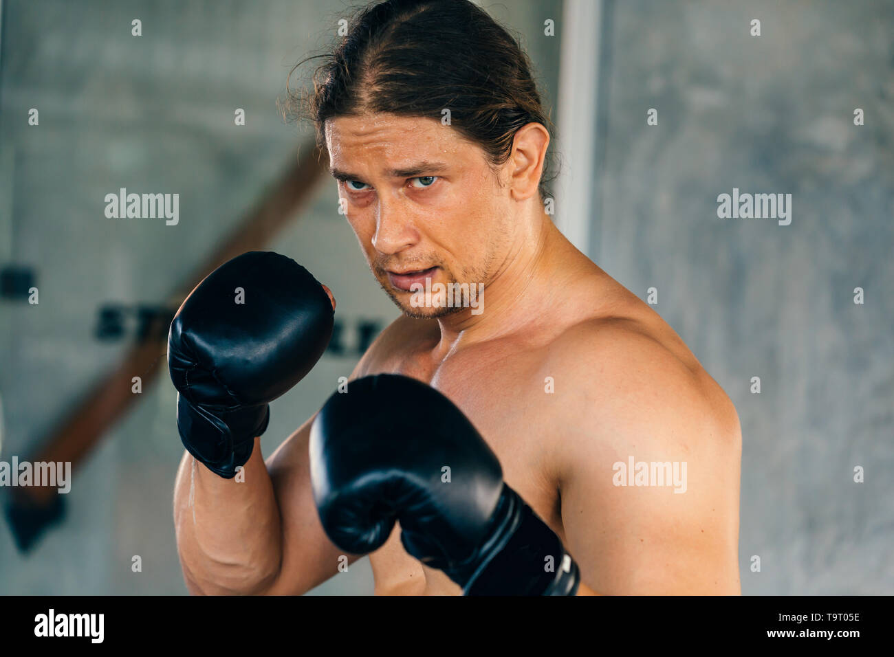 Young Caucasian male boxer wearing boxing gloves in shirtless and boxing stance looking at opponent - Stock Image