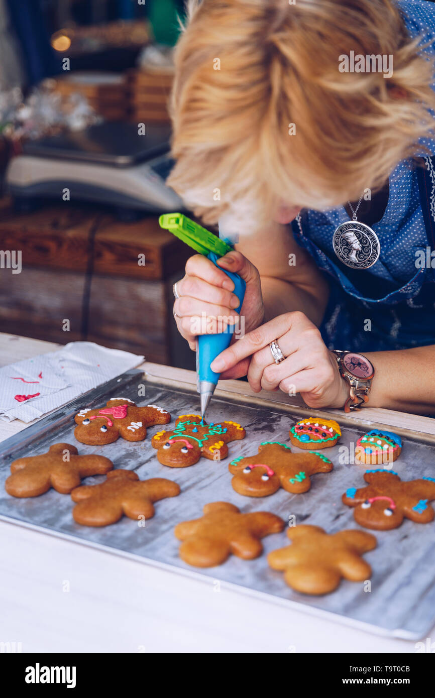 Unrecognizable women confectioner hand decorating a gingerman with a pastry bag, drawing a smile, making it cute, fun and delicious. Woman making ging - Stock Image
