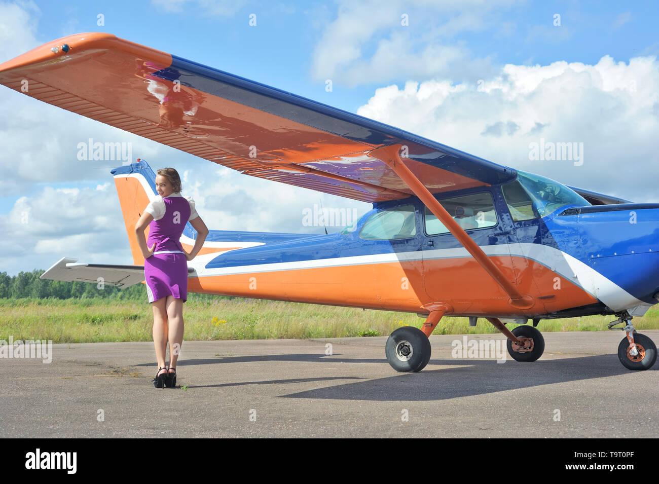 Pretty flight attendant near the small plane outdoors - Stock Image