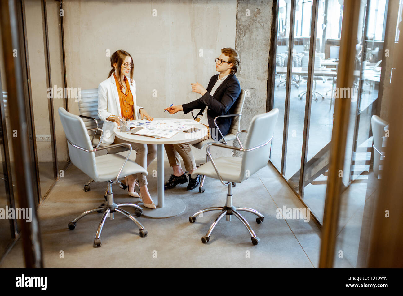 Young Man And Woman Having A Business Conversation During The Small Conference Sitting At The Round Table In The Meeting Room Stock Photo Alamy