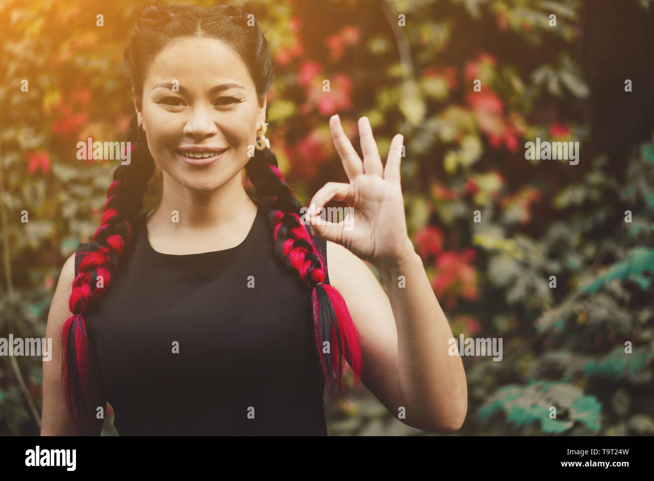 Okay Gesture by Positive Smiling Asian Female. Happy Mature Asian Woman on Summer Nature Background. Positive Lifestyl e Shot. - Stock Image