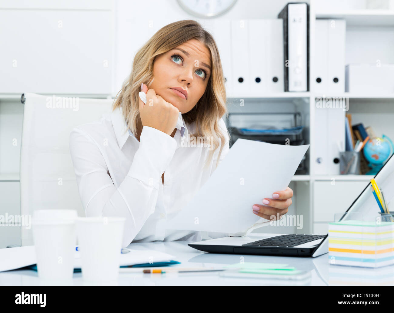Thoughtful young girl in corporate-type clothes in well-lit office - Stock Image