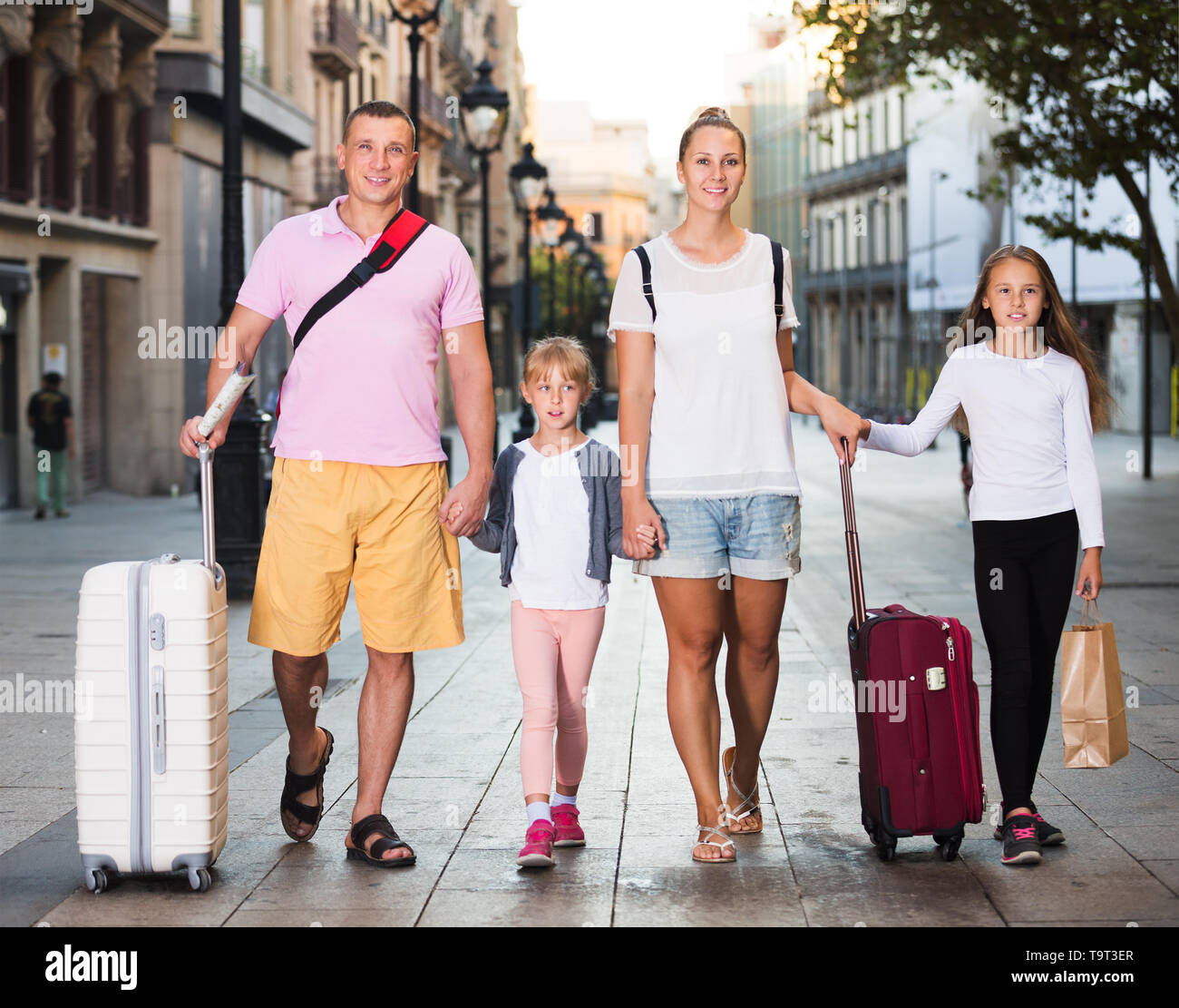 Parents with two kids travelling together on city, walking with luggage - Stock Image