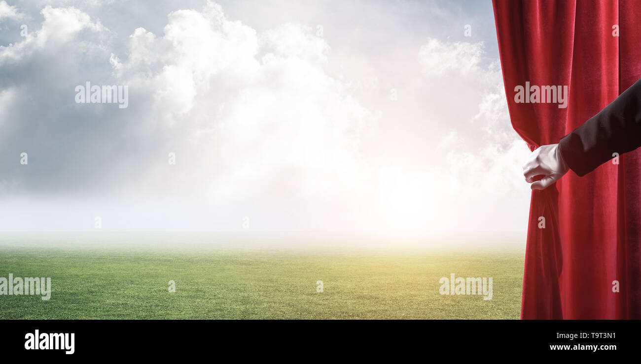 Green meadow behind red curtain and hand holding it - Stock Image