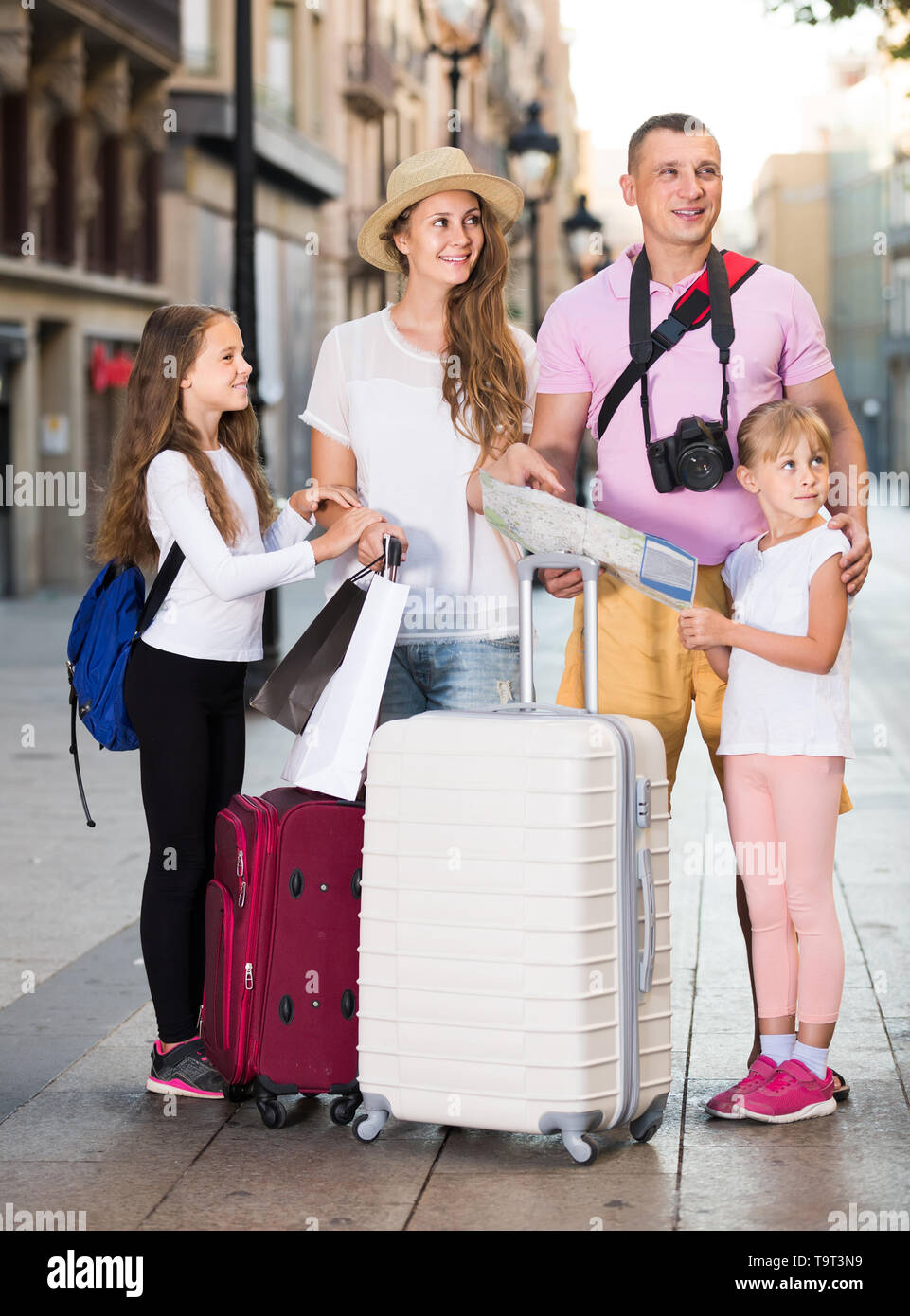 positive british  parents with two kids traveling together searching location on paper map - Stock Image