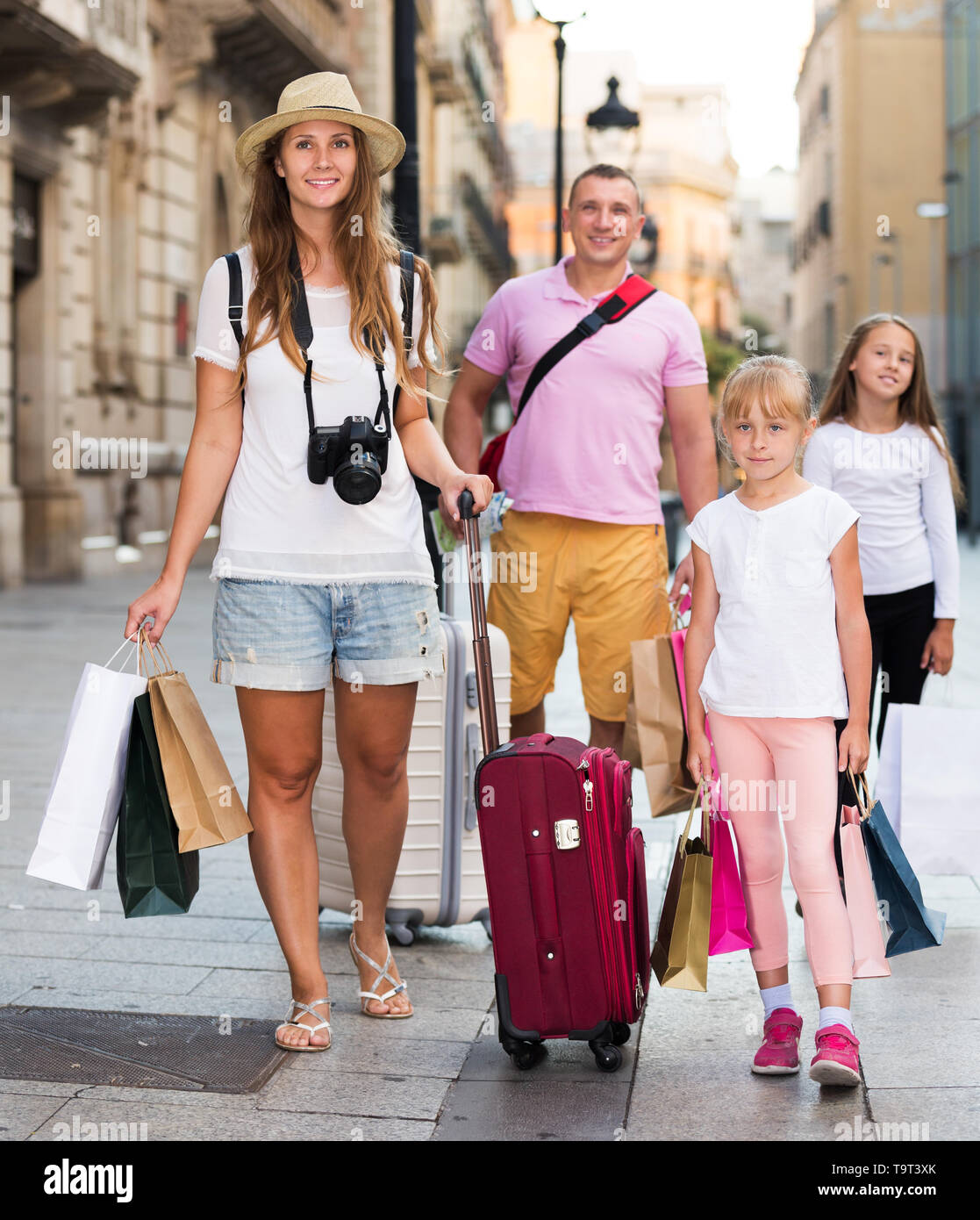 Couple with two kids travelling together on city, walking with baggage - Stock Image