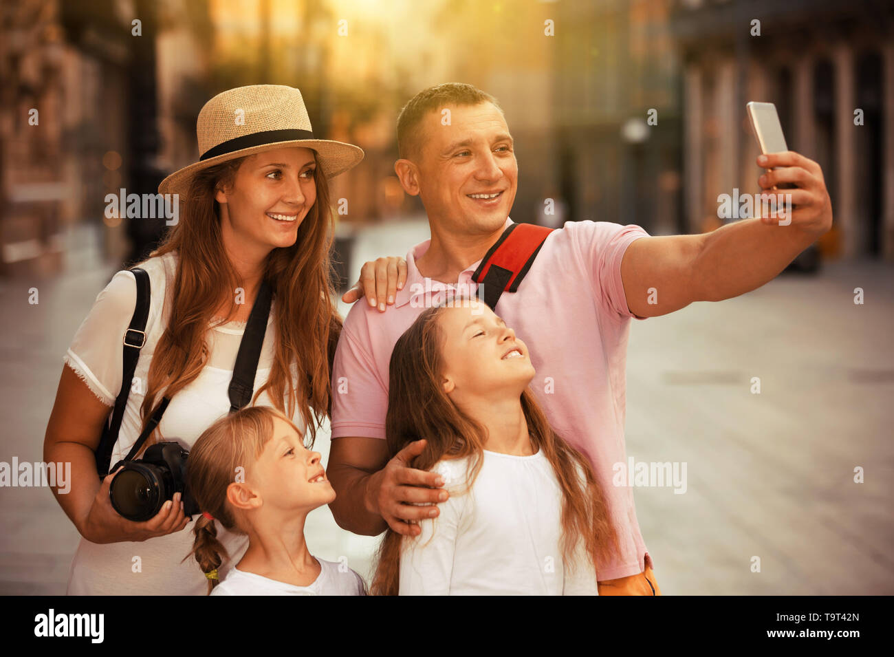 Joyful parents with two kids taking selfie near city sights - Stock Image