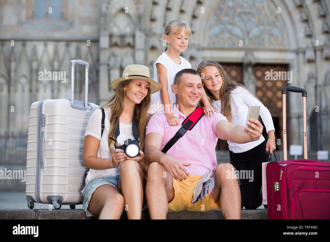 Cheerful parents with two kids taking selfie near city sights - Stock Image
