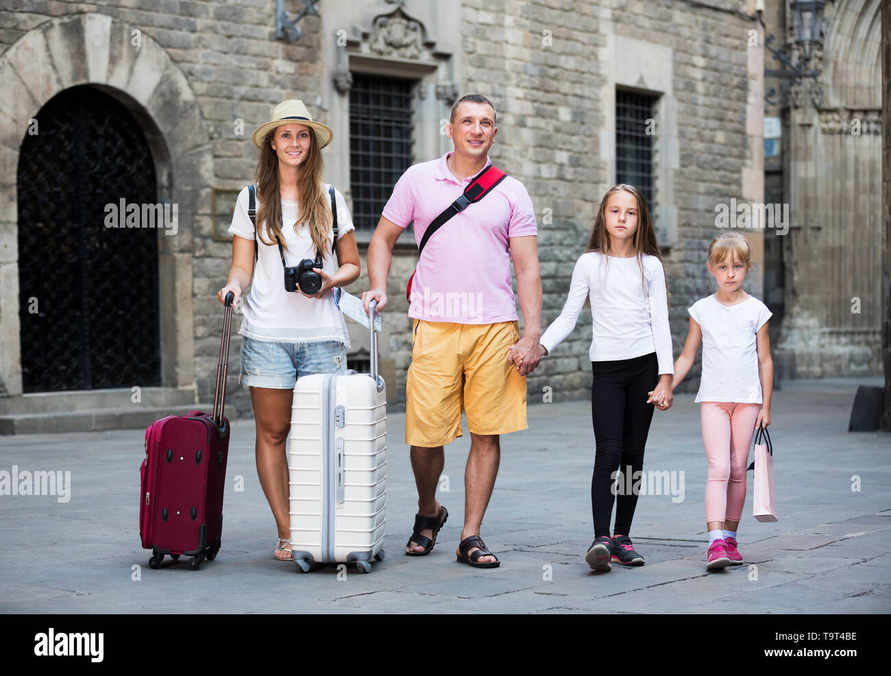 Family couple with two kids travelling together on European city, walking with baggage - Stock Image