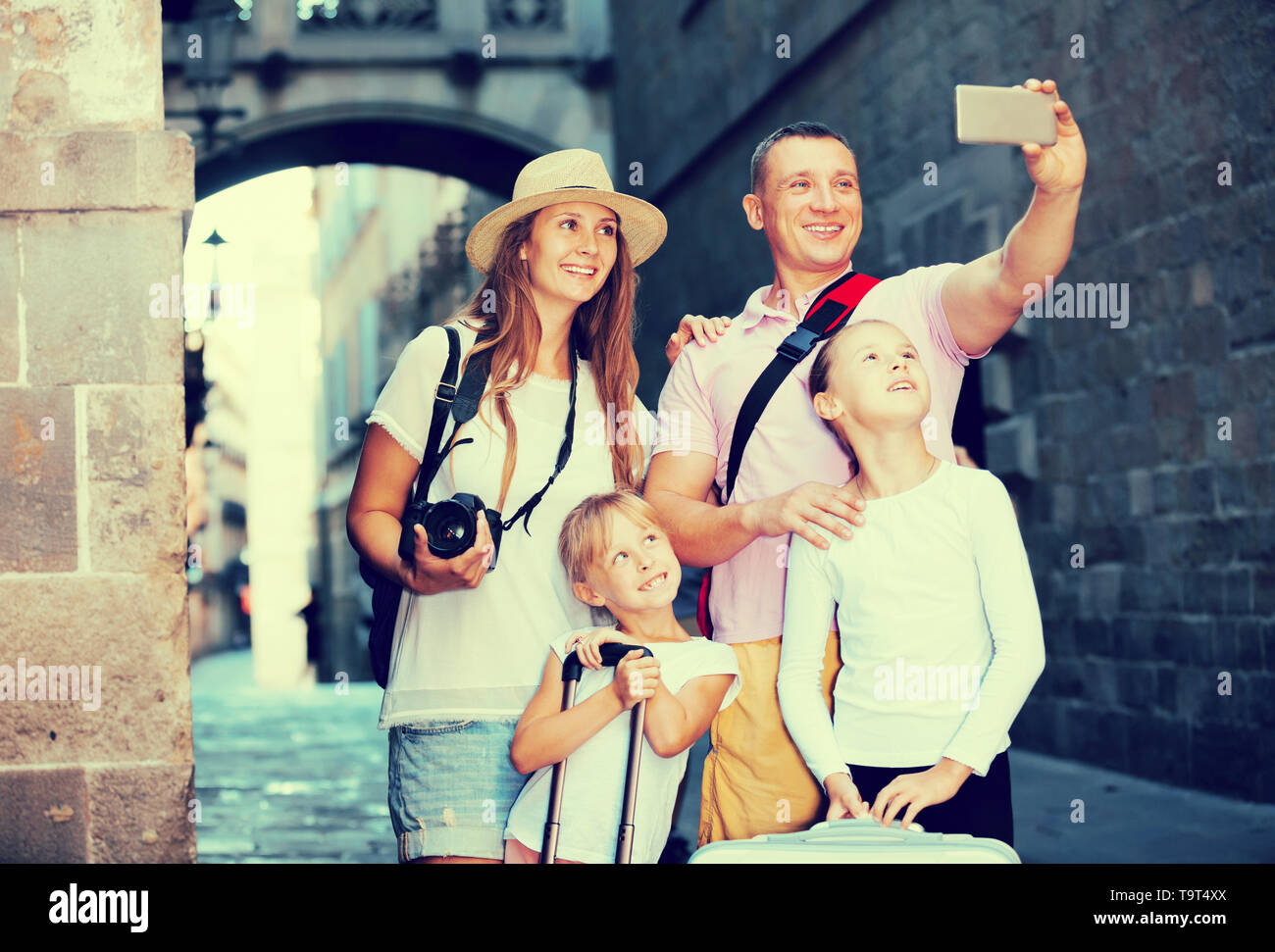 Laughing parents with two kids taking selfie near city sights - Stock Image