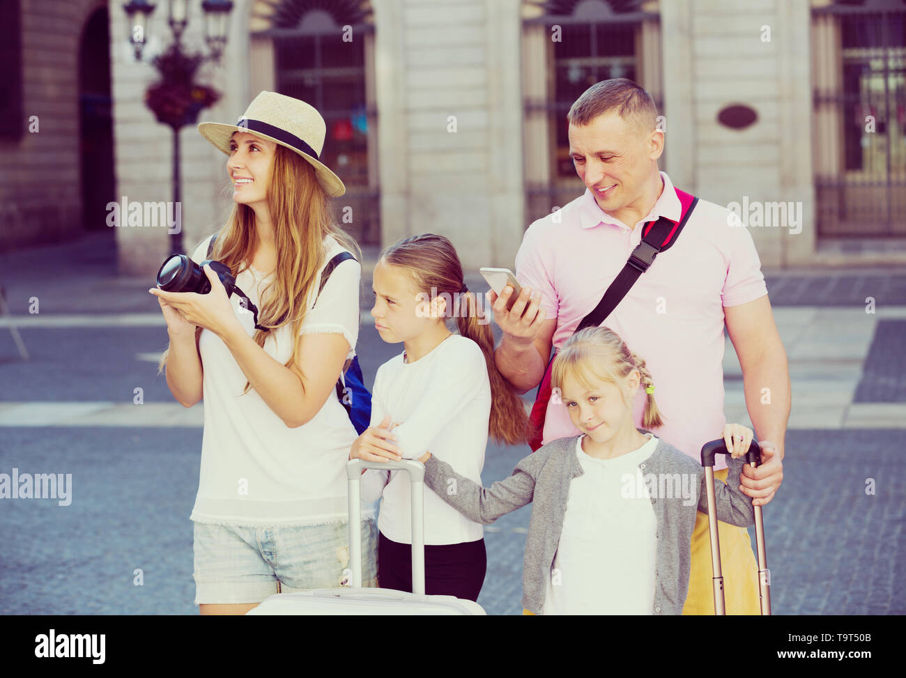 Cheerful parents with two kids using smartphone and photographing sights during their travel - Stock Image