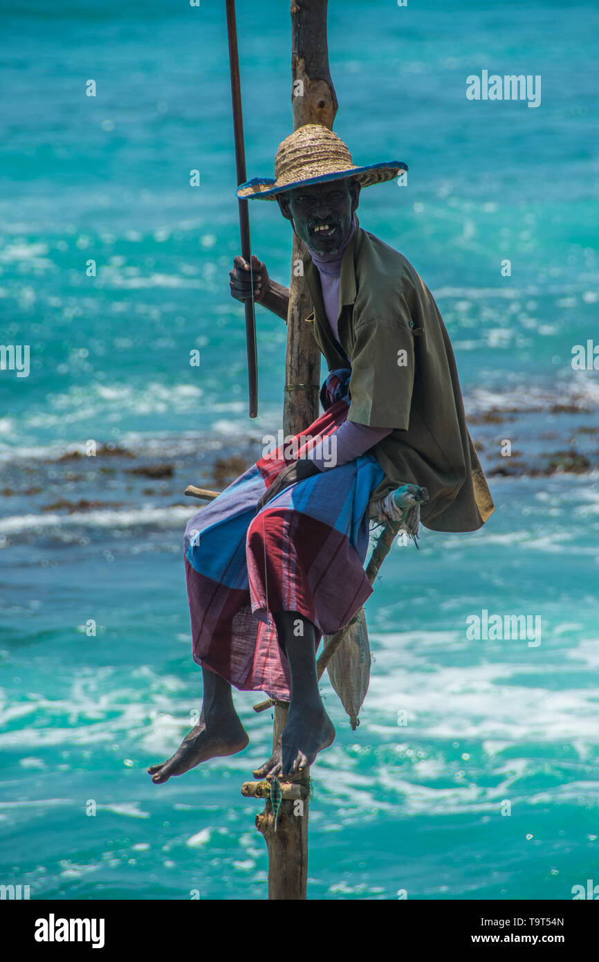 Sri Lanka trip, day 12: this stilt fisherman in Weligama Bay had either caught the small fish on the end of his line (near left foot) or was using it  - Stock Image
