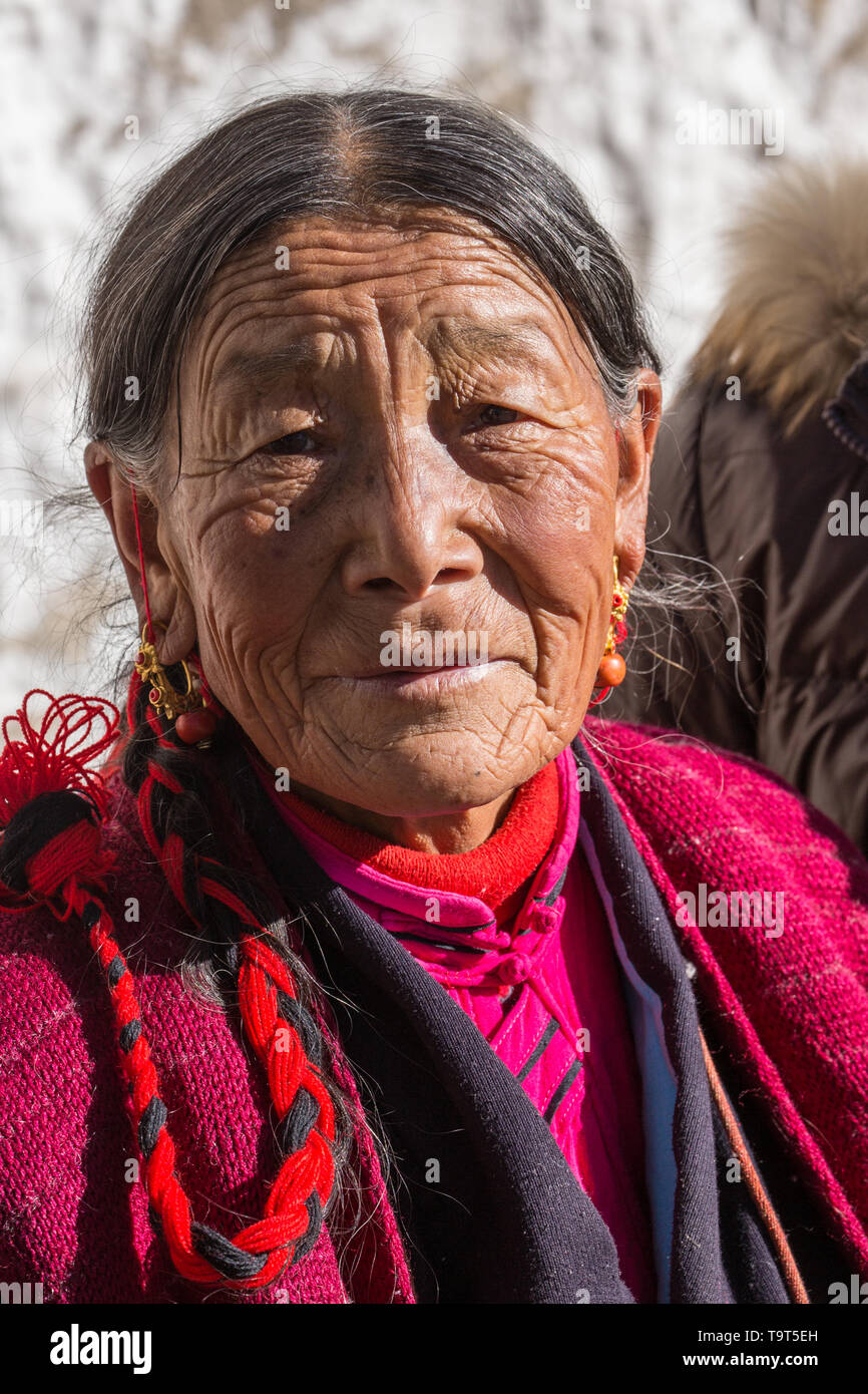 An older Tibetan woman on a pilgrimage to visit the Drepung Buddhist Monastery near Lhasa, Tibet. - Stock Image