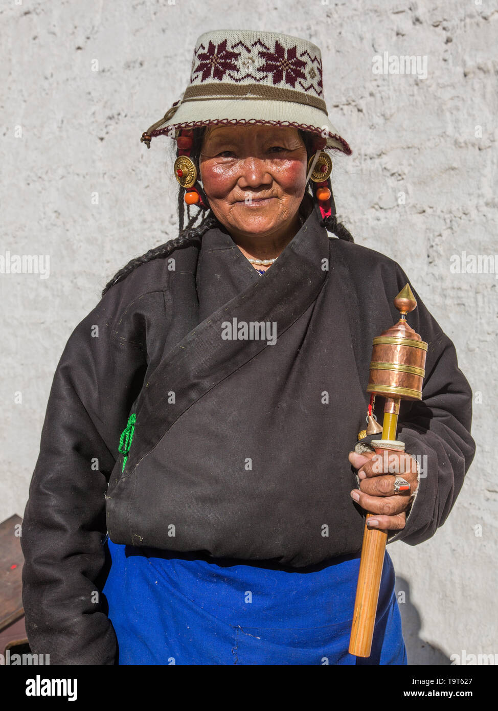 A Khamba Tibetan woman from the Kham region of eastern Tibet on a pilgrimage to visit holy sites in Lhasa, Tibet.  She is wearing red coral jewelry in - Stock Image
