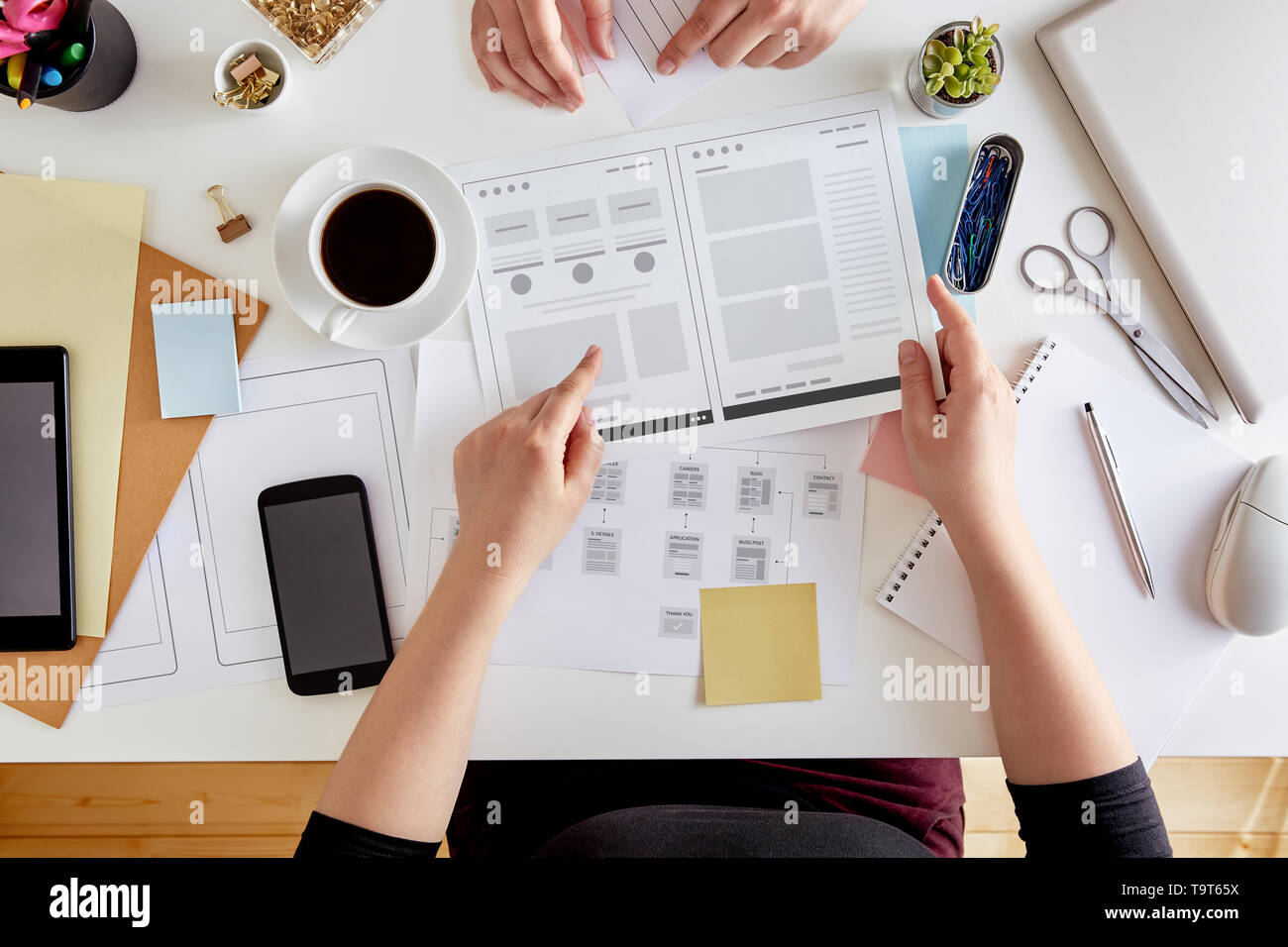 Overhead view of young UX designers planning out the structure of a website. Wireframing stage of a web design project - Stock Image
