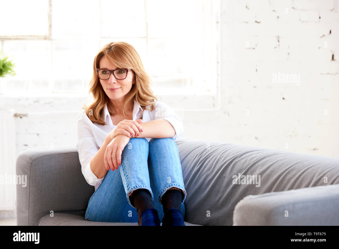 Portrait shot of thinking middle aged woman relaxing on sofa. - Stock Image