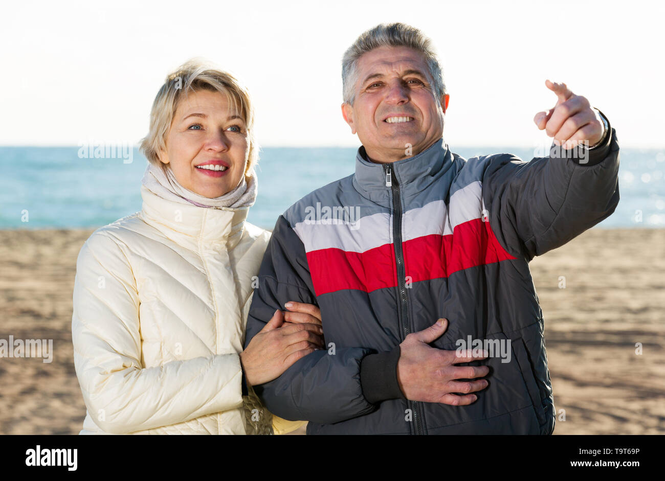 Cheerful mature couple walks outdoors and point by hand to interesting objects - Stock Image