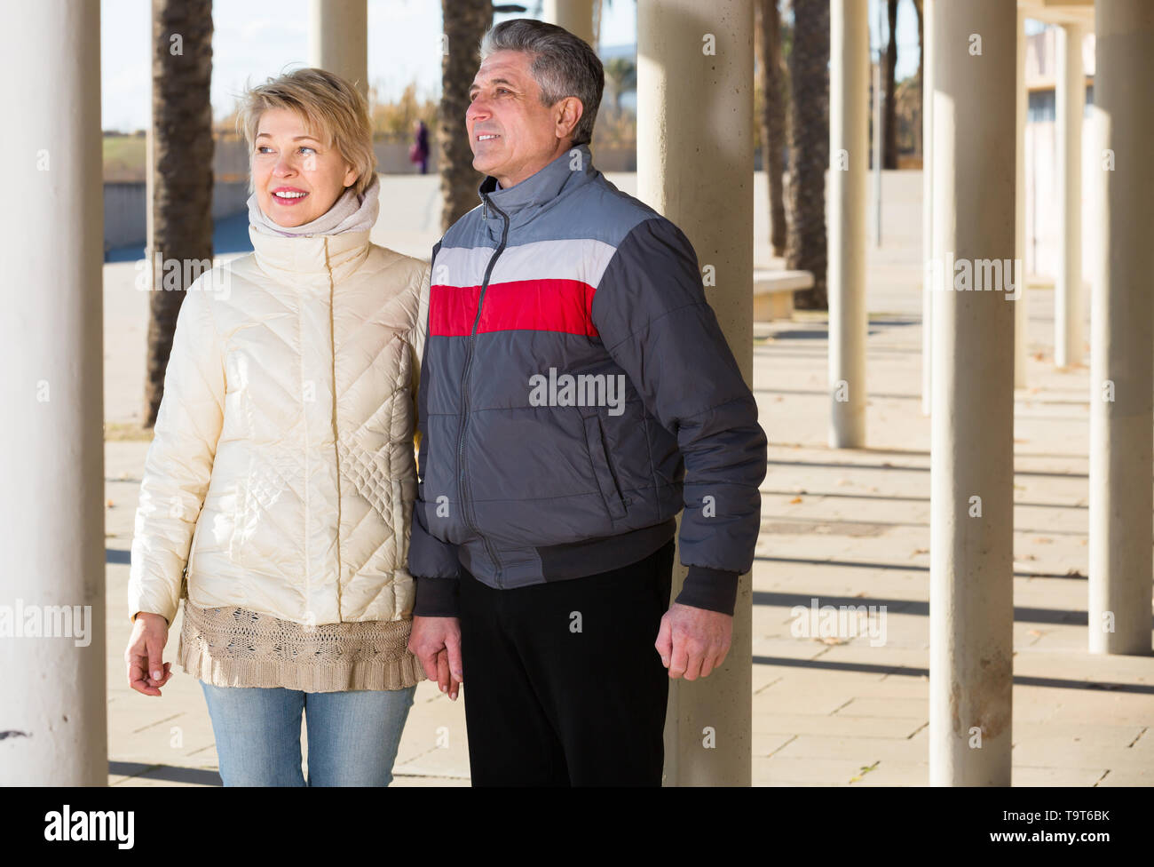 Smiling husband and wife are walking together clear sunny day between columns - Stock Image