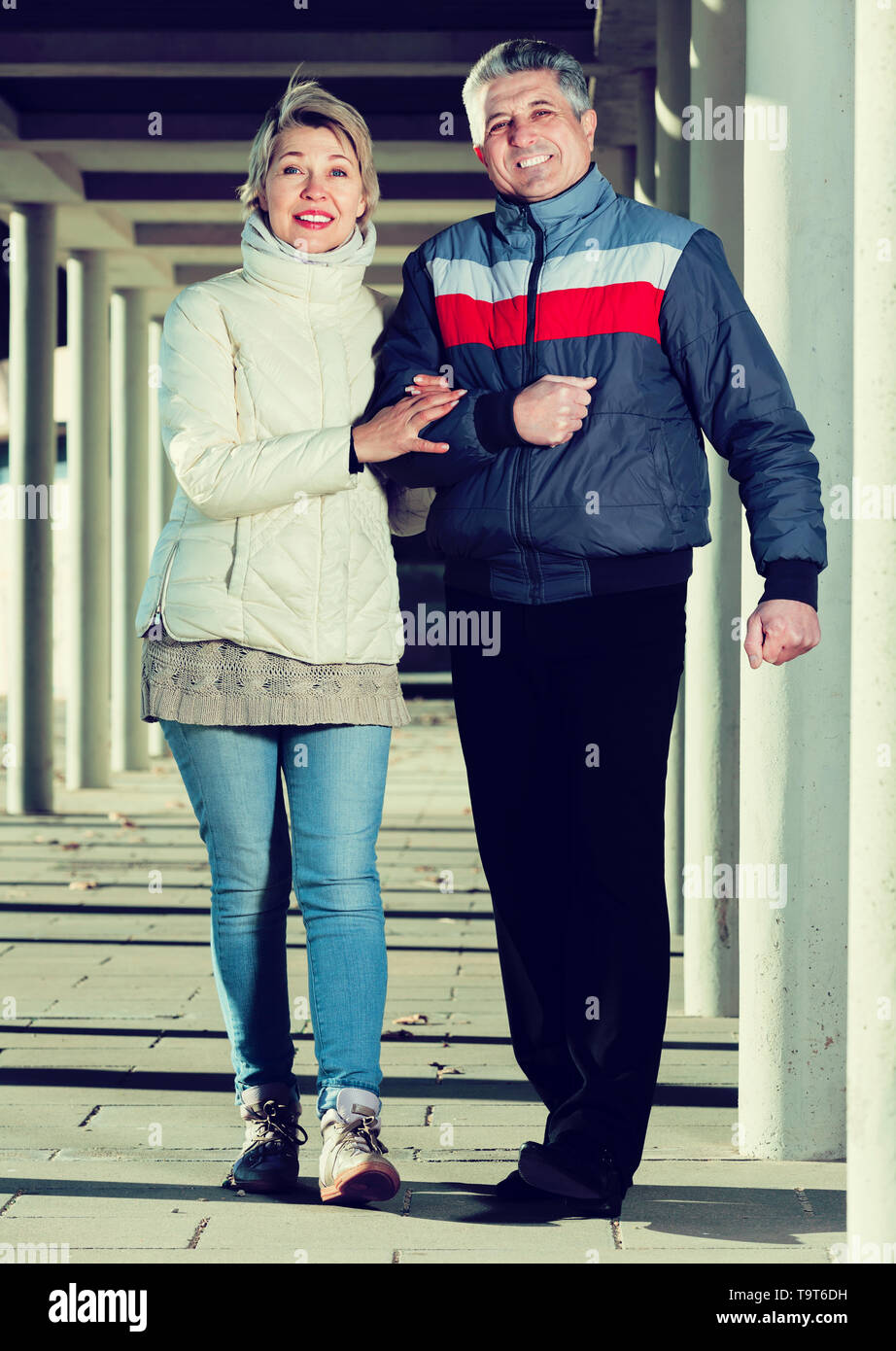 Positive aged couple walking along corridor fenced with columns - Stock Image