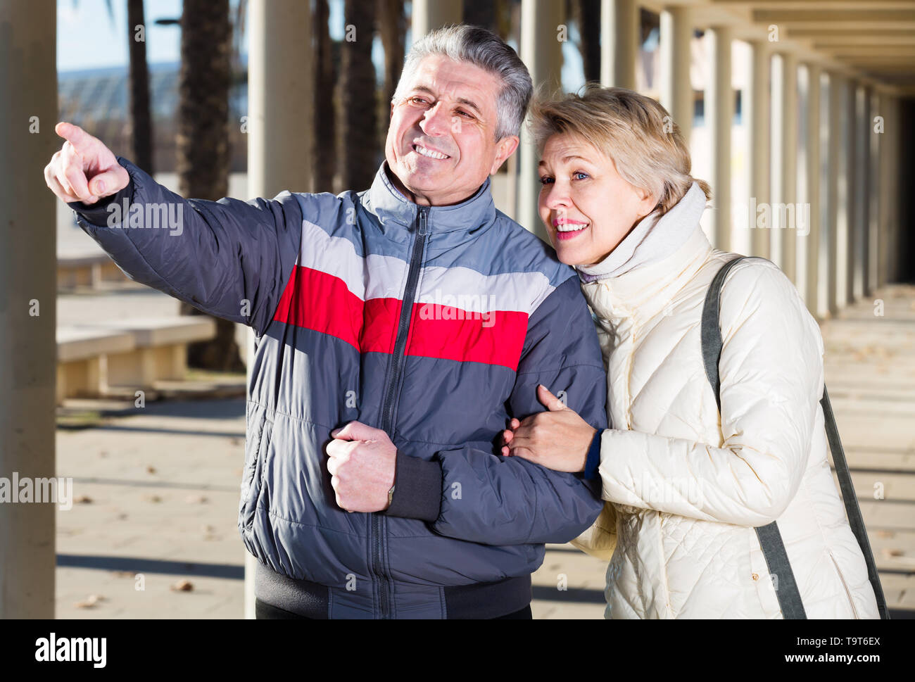 Mature married couple walk and husband points to wife to something interesting - Stock Image