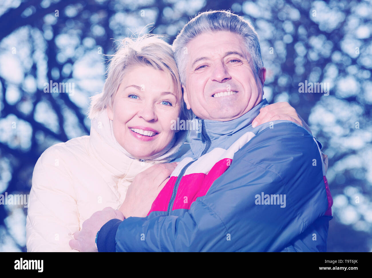 Smiling mature married couple embracing on sunny day in park - Stock Image