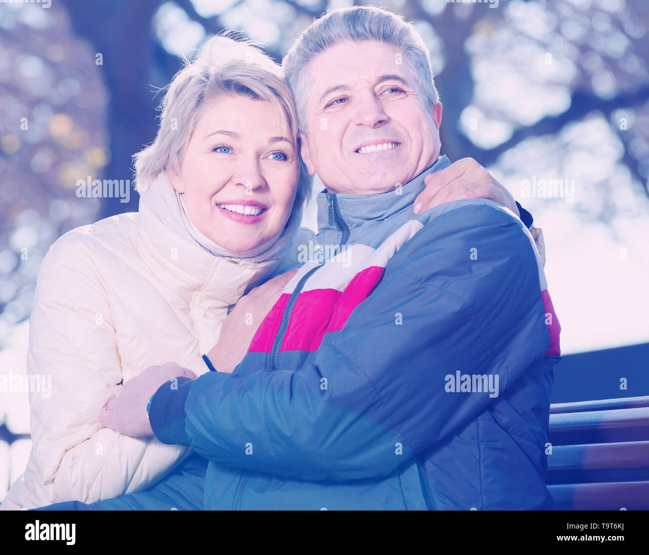 mature couple sitting on park bench on sunny day - Stock Image