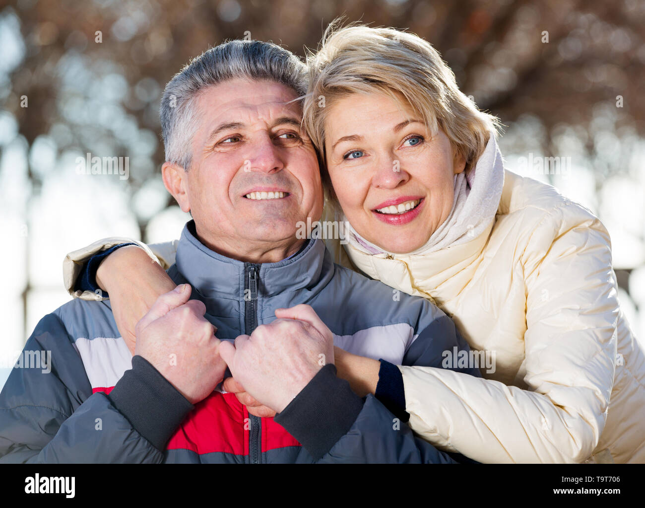 Glad mature married couple embracing on sunny day in park - Stock Image
